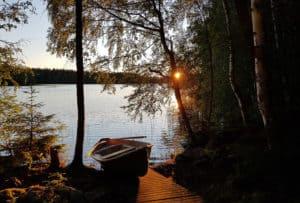 Mökkeily Auringonlasku järvenrannalla