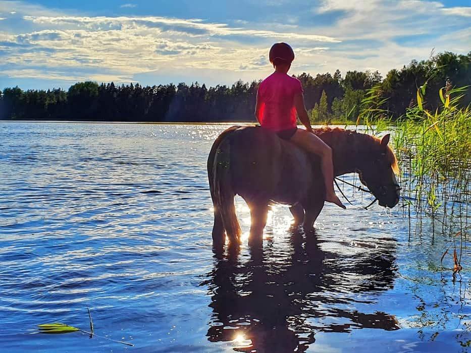 Hevoshäme ratsastamassa hevosen kanssa järven rannassa