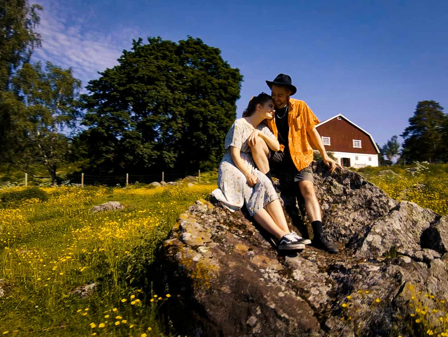 Nuori pariskunta istuu kivellä maalaismaisemassa