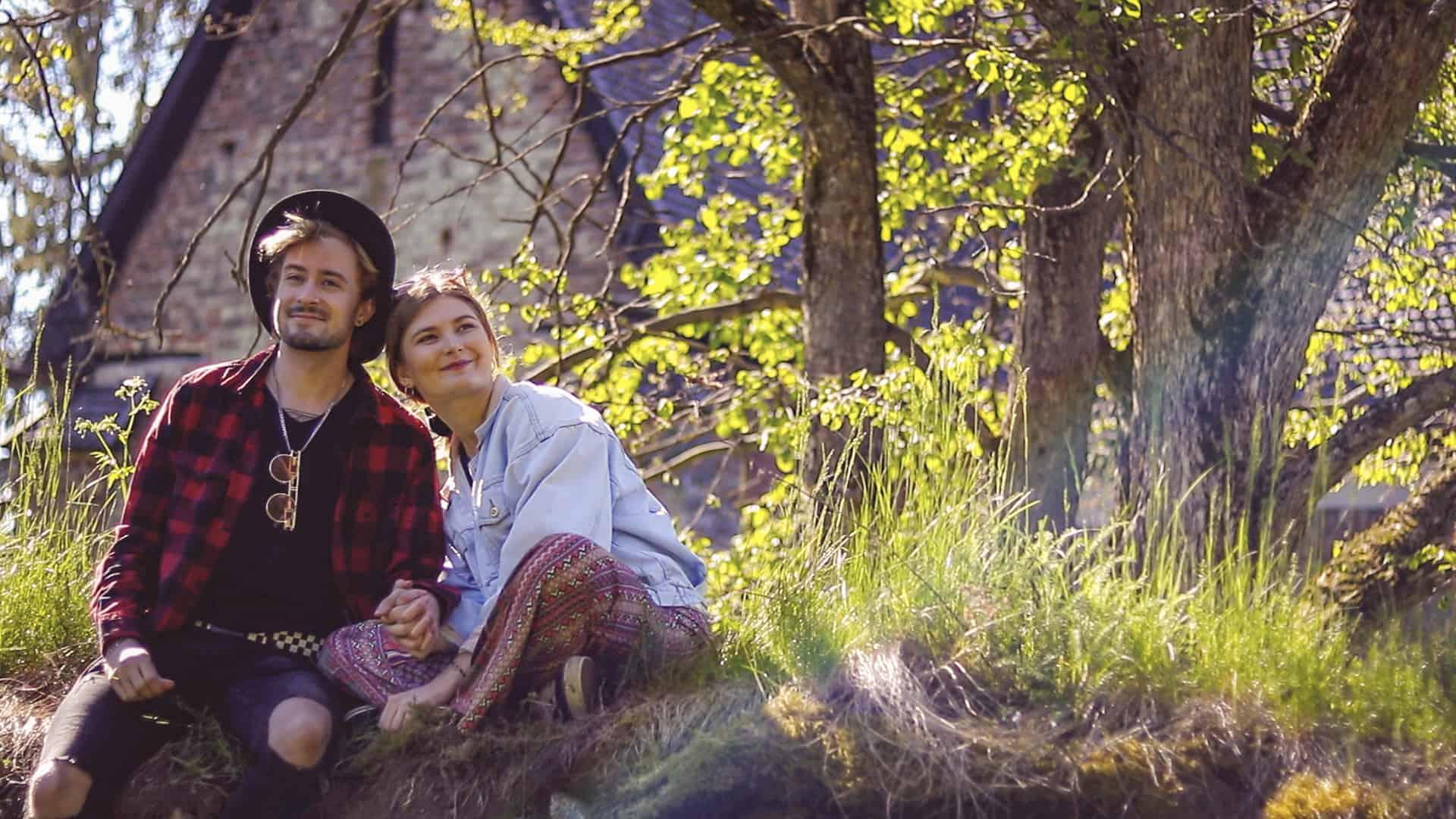 Nuori pariskunta istuu aidan päällä kirkkomaisemassa