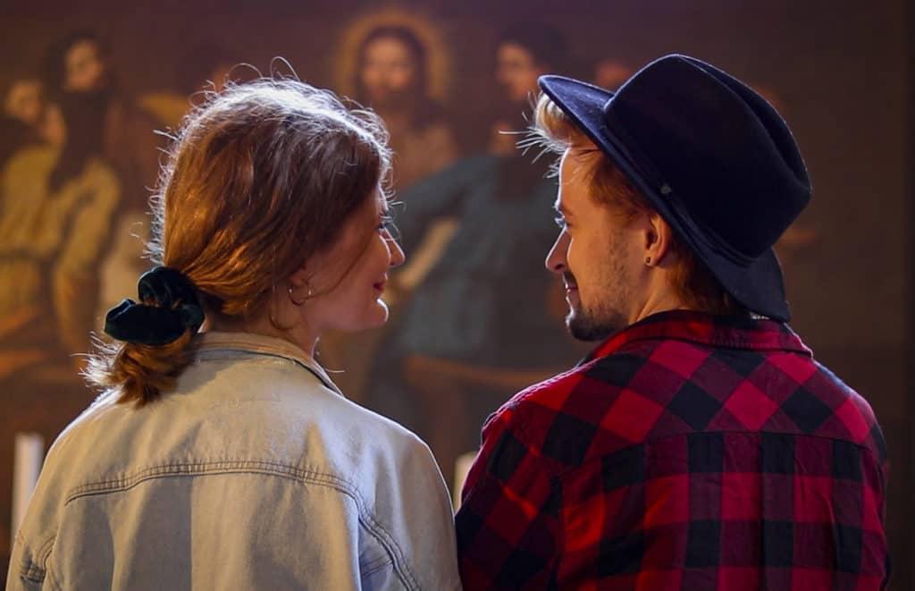 Nuori pariskunta katsoo toisiaan kirkon sisällä